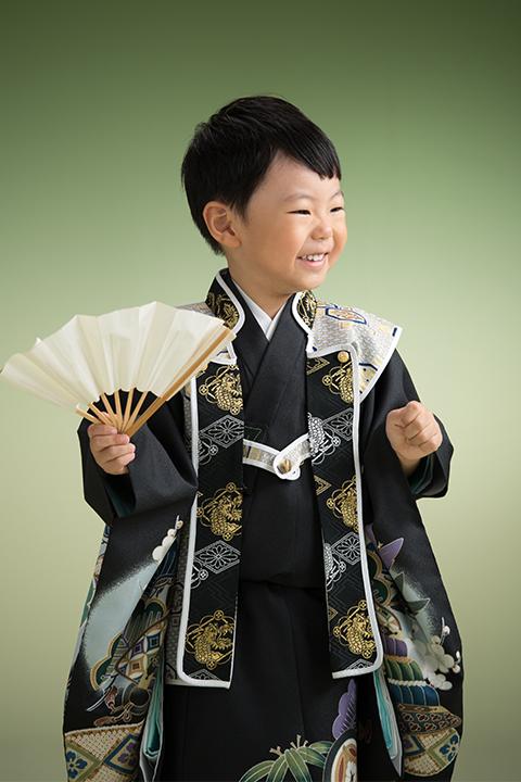 扇を持って笑顔の陣羽織を着た男の子